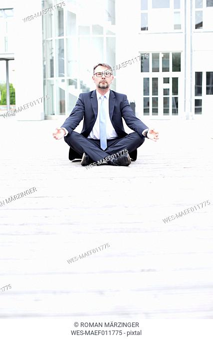 Businessman sitting outdoors meditating