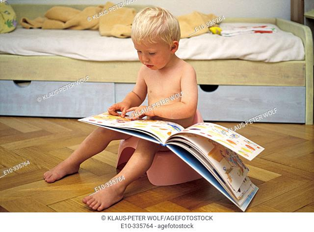 2 year old boy sitting on the pot and looking at a picture book