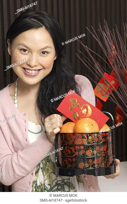 Woman with basket of oranges and red packet
