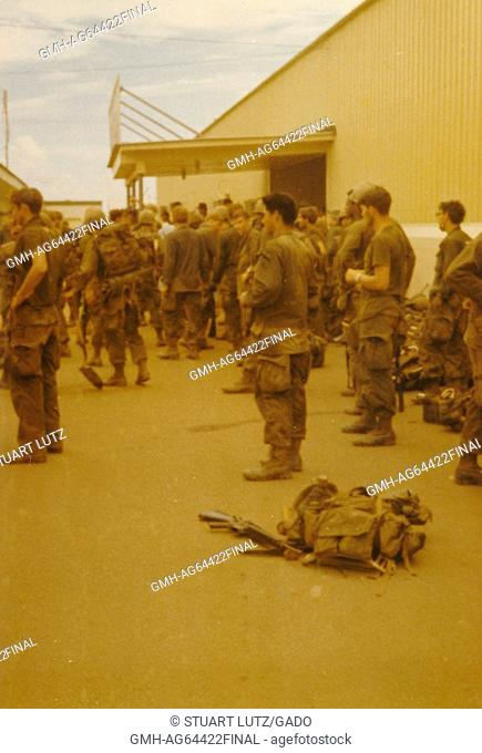A large group of soldiers are gathered in their uniforms, all facing the same direction, their combat gear has been placed to the side against a building