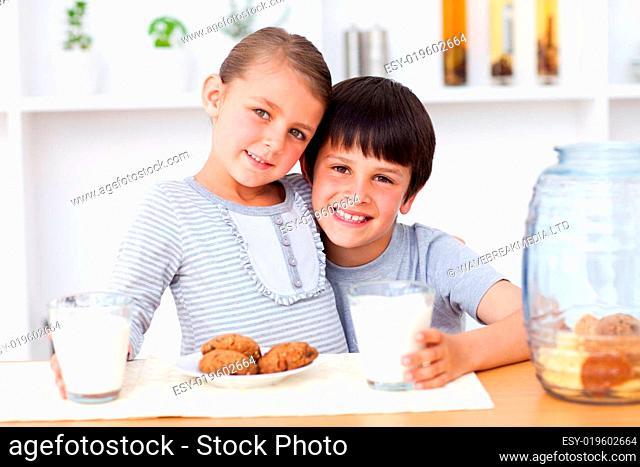 Portrait of happy siblings eating biscuits