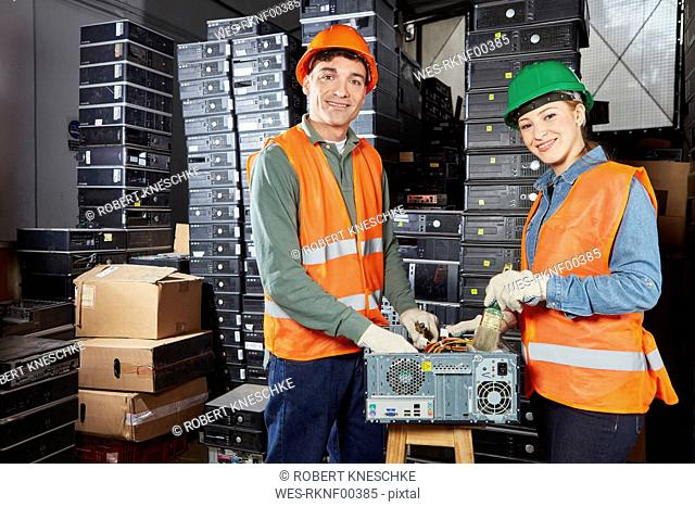 Workers in computer recycling plant cleaning pc casing