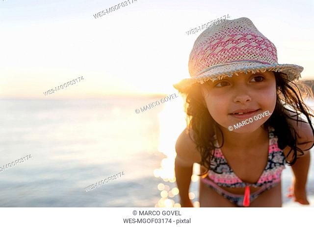 Spain, Menorca, girl on the beach at sunset