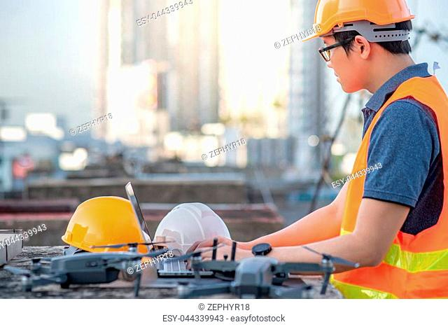 Young Asian man working with drone laptop and smartphone at construction site. Using unmanned aerial vehicle (UAV) for land and building site survey in civil...