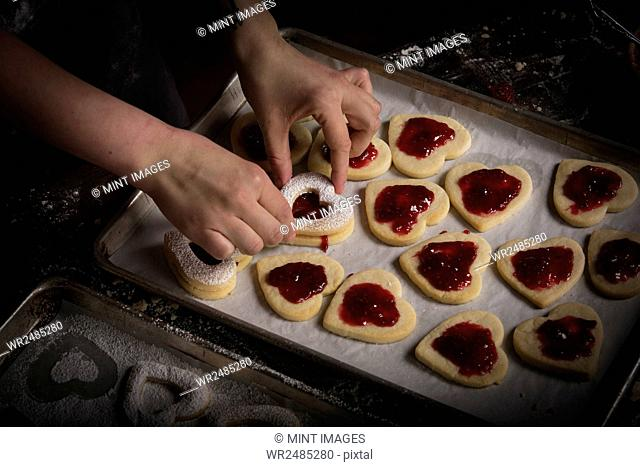 Valentine's Day baking, woman spreading raspberry jam on heart shaped biscuits