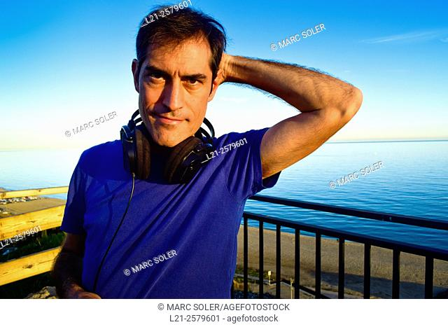 Man with headphones hanging on the neck behind a railing near the sea. He is wearing a blue t-shirt