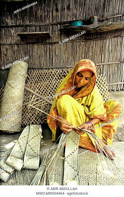 A woman works with the stems of some palm or coconut leaves used in weaving to make some wonderful handicrafts or household items Bangladesh