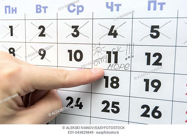 Hand indicates the day on the calendar with the inscription vacation