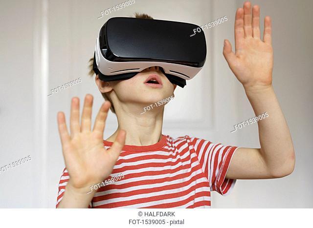 Boy playing virtual reality game at home