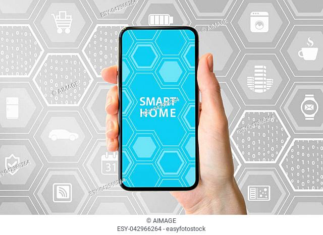 Smart home automation concept with hand holding modern bezel-free smartphone in front of neutral background with icons of appliances