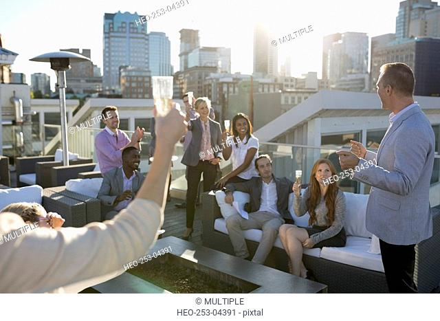 Business people toasting champagne on sunny urban rooftop
