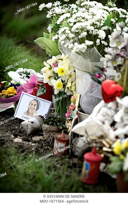 Giulia Spinello's picture surrounded by church candles and bunches of flowers on the road edge, where the girl was knocked down and killed