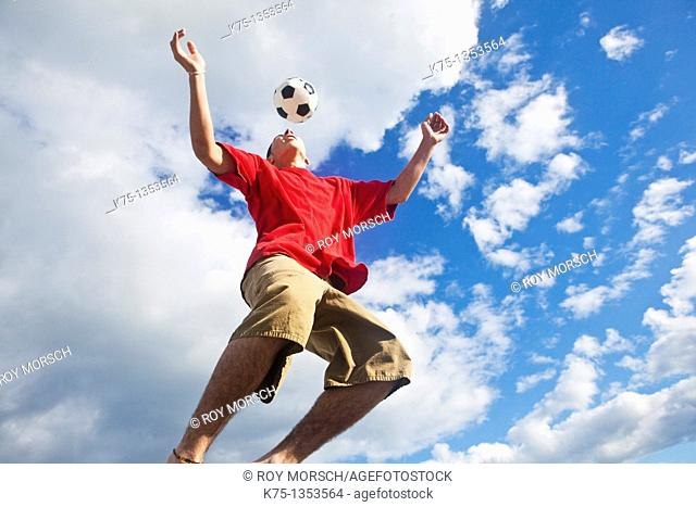 teen hits soccer ball high in the sky