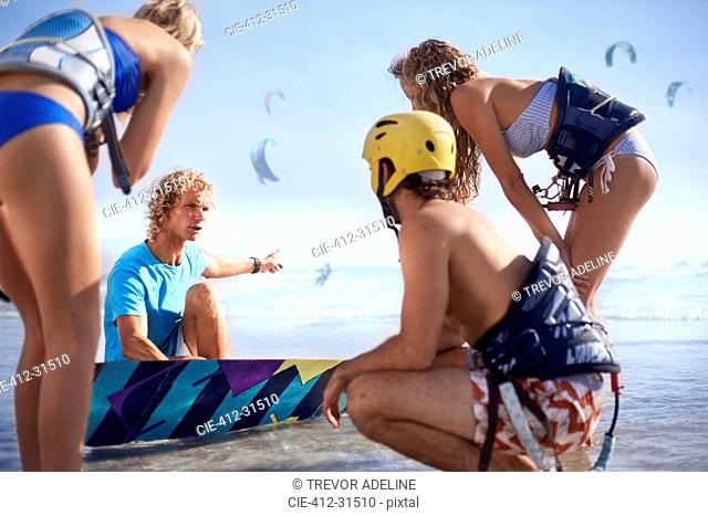 Man teaching friends kiteboarding on sunny beach