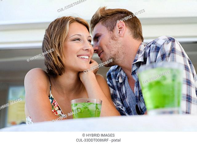 Couple whispering together at cafe