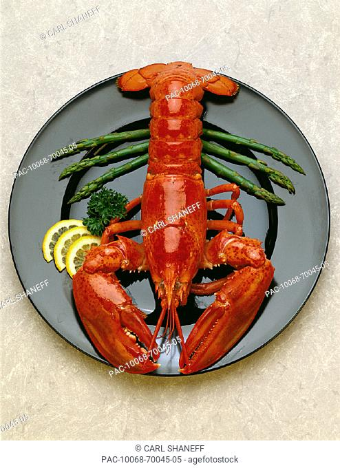 Plate with whole lobster, lemon slices, and asparagus spears B1127