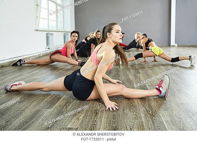 Confident female dancers doing splits while dancing on floor at studio