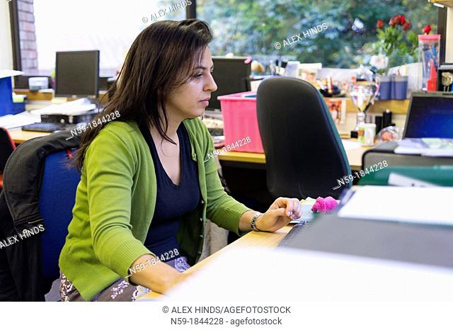 Female teacher working at her desk in staffroom