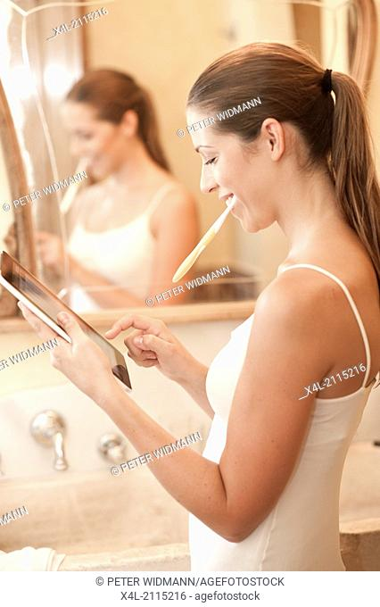 young, pretty woman in bathroom, mit digital tablet (model-released)