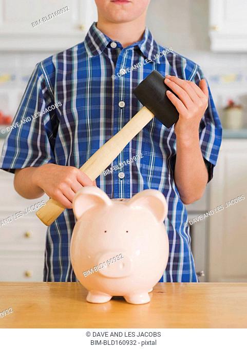 Caucasian boy holding sledgehammer over piggy bank