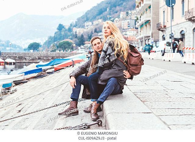 Young couple sitting on lakeside, Lake Como, Italy