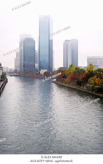 Osaka city downtown Chuo-ku financial distric Okawa River and high-rise towers, Crystal tower and others in colorful autumn foggy urban scenery