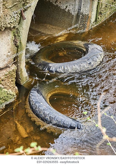 Pollution of the environment. Old tires thrown in a stream in whose waters there is a glass bottle
