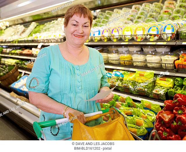 Hispanic woman holding shopping list in grocery store