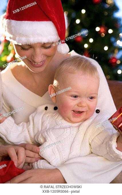 mother with baby next to christmas tree