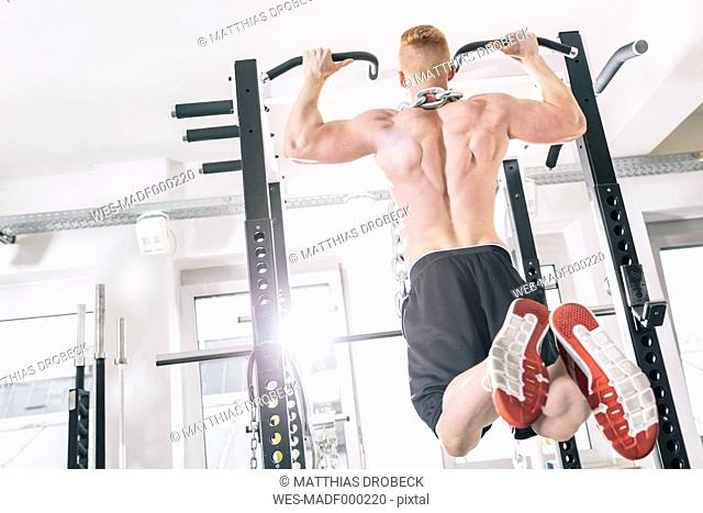 Young man exercising chin-ups on power rack in gym