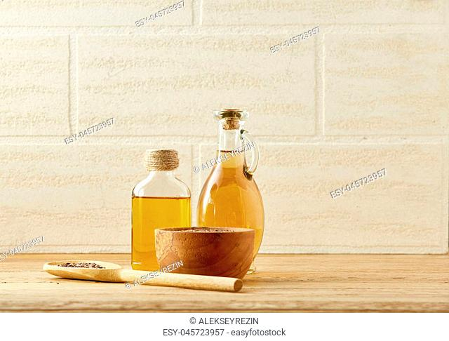 Composition of two transparent glass oil jars, wooden bowl with flax seeds and a scoop on wooden table over a light background, selective focus