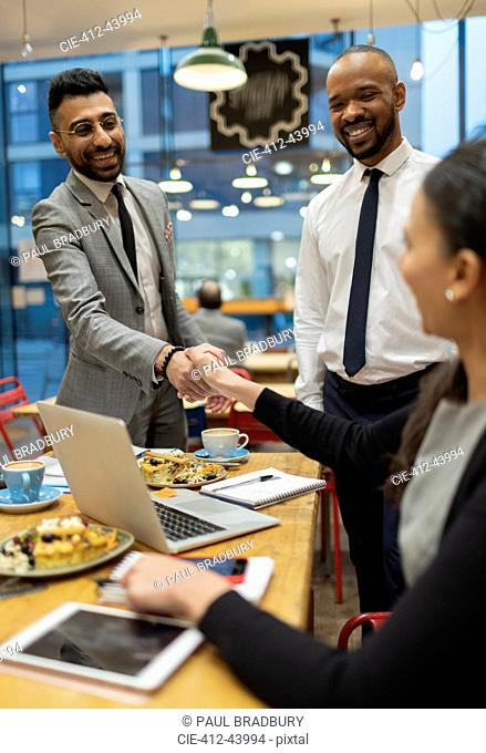 Business people handshaking, working in cafe