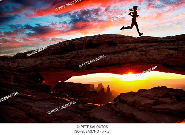 Young female runner running over rock formation at sunset, Moab, Utah, USA