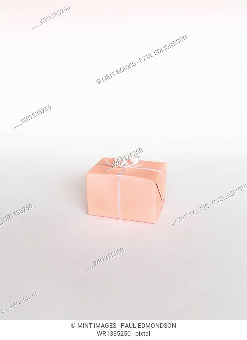 A small boxed gift wrapped in pink paper with a ribbon, on white background
