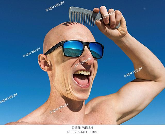 A guy with a bald head holds a comb over his hairless head while wearing sunglasses and a big smile; Tarifa, Cadiz, Andalusia, Spain
