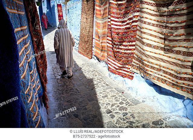 Moroccan man wearing djellaba, walking through the Medina. Colorful carpets hanging from walls. Chaouen, Morocco