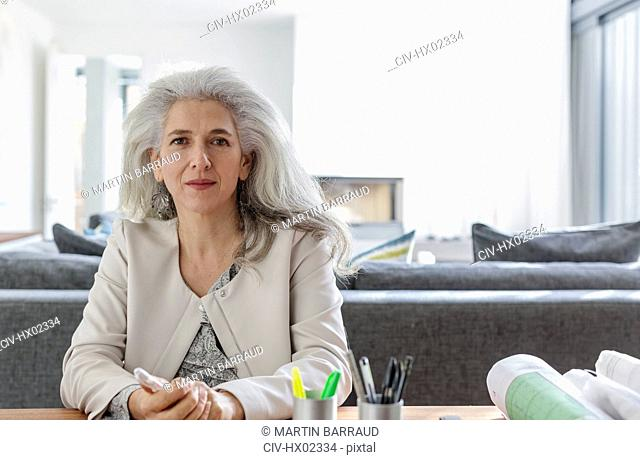 Portrait confident female architect in home office