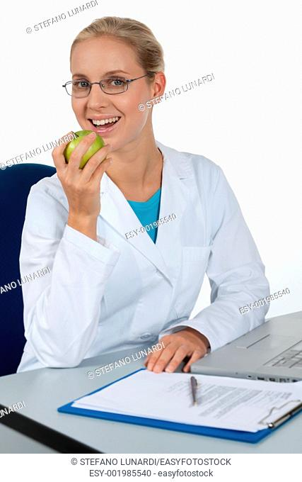 Beautiful female doctor eating an apple while working in her office