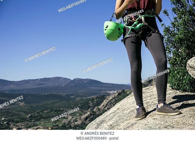 Legs of a climber woman with climbing equipment