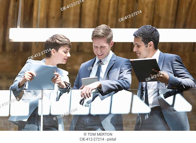 Business people with digital tablet on office balcony