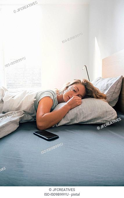 Smartphone on bed, young woman asleep