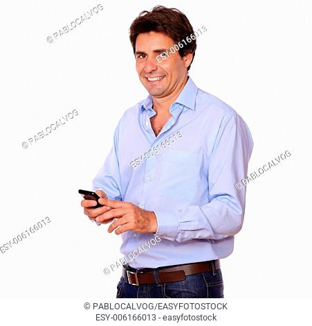 Portrait of a stylish hispanic man texting on cellphone while standing on white background