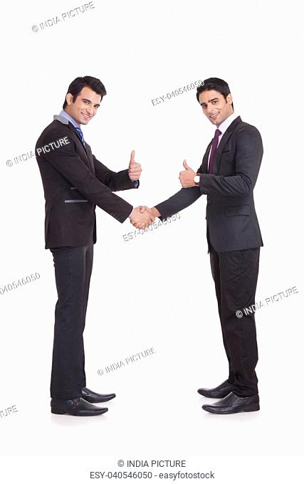 Portrait of two businessmen giving thumbs up
