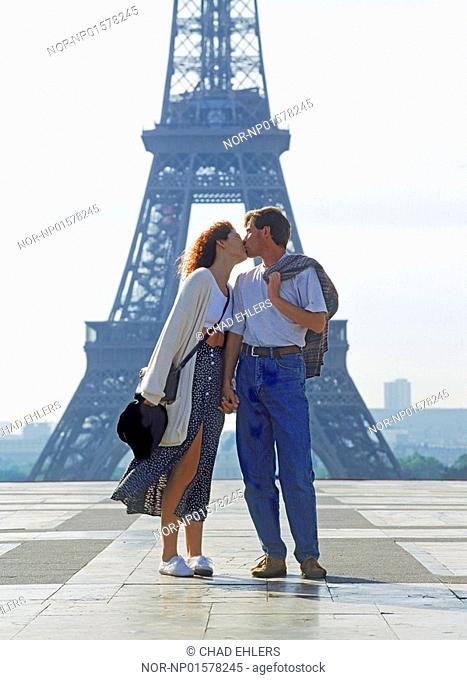 Couple kissing at Palais de Chaillot in Paris with Eiffel tower in background