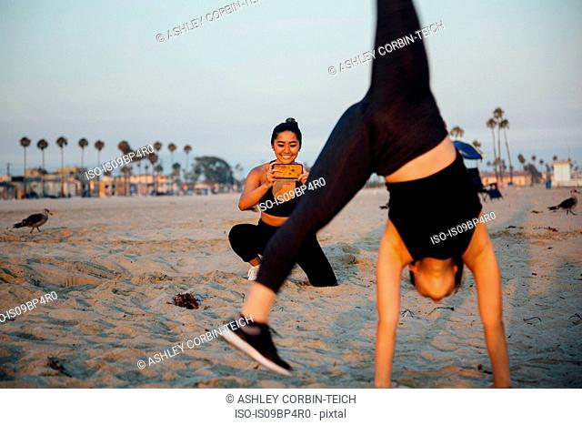 Friends photographing exercise on beach, Long Beach, California, US
