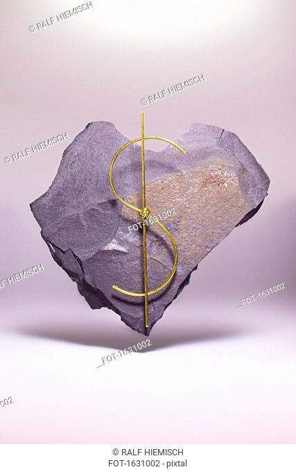Dollar sign made of metallic wire on heart shape stone against white background