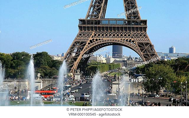 Mid shot of the Eiffel Tower at Champ de Mars in Paris, with traffic and people and the fountains