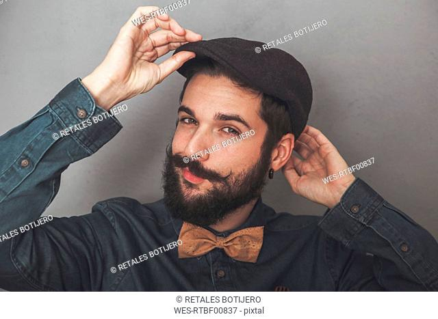 Bearded man putting on his cap, wearing denim shirt and cork bow tie