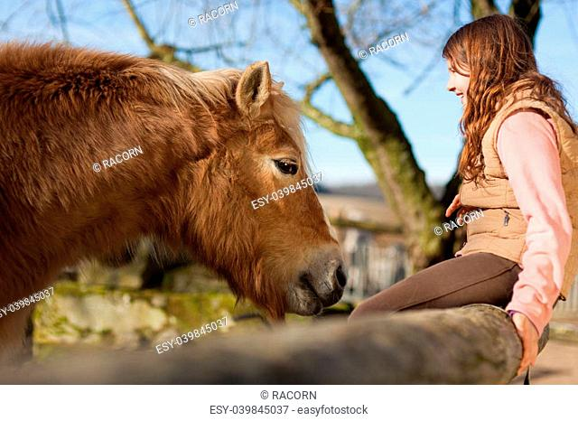Smiling young girl and her palomino color horse in the outdoors