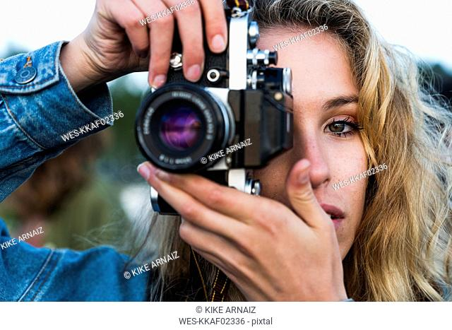 Close-up of beautiful blond young woman taking a picture with a camera